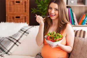 אישה בהריון אוכלת קערת סלט