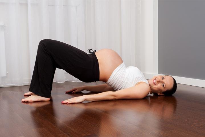 אישה בהריון עושה תרגיל גשר