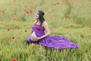 אישה בהריון בשמלה סגולה