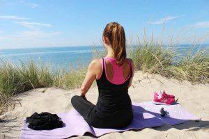 אישה עושה יוגה אל מול החוף