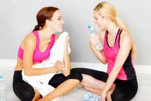 שתי נשים מחייכות במהלך אימון כושר