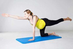 אישה בהריון עובדת על חיזוק שרירי הליבה והישבן