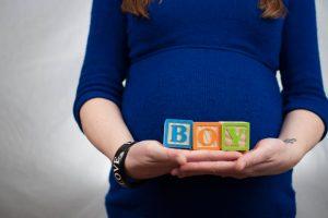 אישה בהריון עם שלט שזה בן
