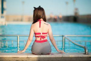 בחורה יושבת על שפת הבריכה