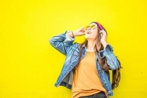 נערה מחייכת נשענת על קיר צהוב