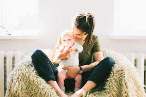 אישה אוחזת את התינוק שלה בישיבה