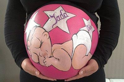 בטן של אישה בהריון ועליה ציור