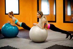 שתי בנות עושות פלאנק על כדור פיטבול