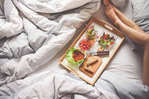 בחורה אוכלת ארוחת בוקר במיטה