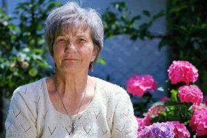 אישה מבוגרת יושבת על ספסל ומאחוריה פרחים