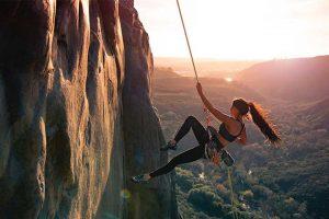 אישה מטפסת על הר גבוה