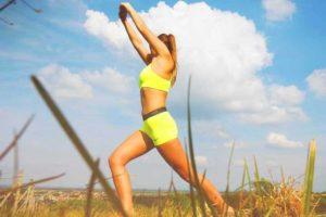 בחורה עם גוף חטוב לובשת גוזיית ספורט צהובה של נייק