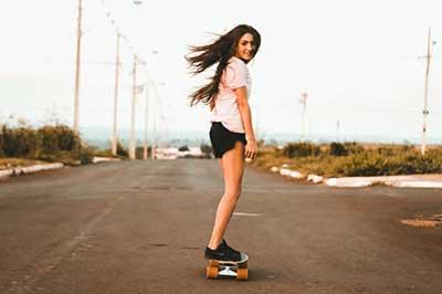 בחורה רוכבת על סקייטבורד בכביש