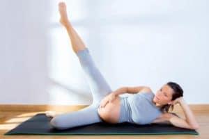 אישה בהריון מתאמנת על המזרן