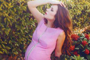 בחורה בהריון לובשת חולצה ורודה