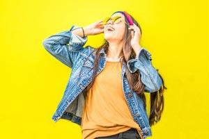 נערה צוחקת נשענת על קיר צהוב