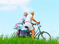 זוג מבוגרים רוכב על אופניים בגינה
