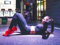 בחורה עושה כפיפות בטן על מזרון יוגה