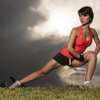 בחורה בכושר מותחת את הרגליים
