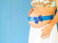 אישה בהריון עם סרט מתנה כרוך סביב הבטן