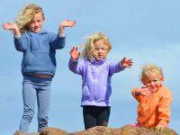 שלושה ילדים מתוקים עומדים על סלע
